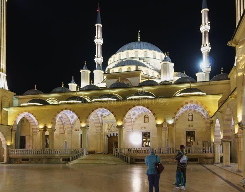 Τουρίστες στη ανοιχτή περιοχή της καρδιάς μουσουλμανικών τεμενών Τσετσενίας Όμορφη νύχτα που ανάβει τη δημοφιλή έλξη στοκ φωτογραφίες