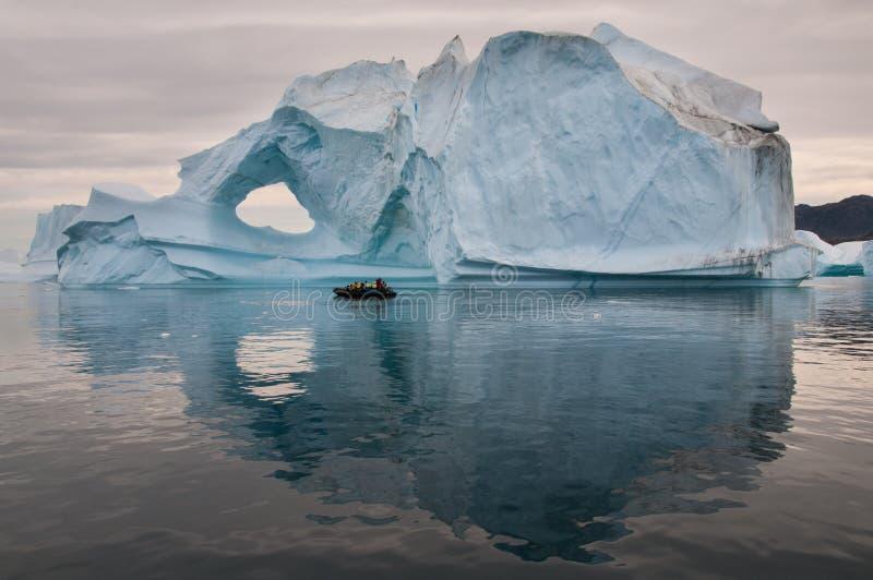 Τουρίστες στη διογκώσιμη λαστιχένια βάρκα μπροστά από το ξεπερασμένο παγόβουνο, Scoresby Sund, Γροιλανδία στοκ εικόνες