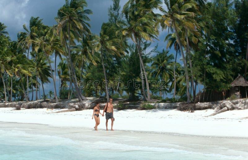 Τουρίστες strolling σε μια άσπρη παραλία σε Zanzibar στοκ εικόνες