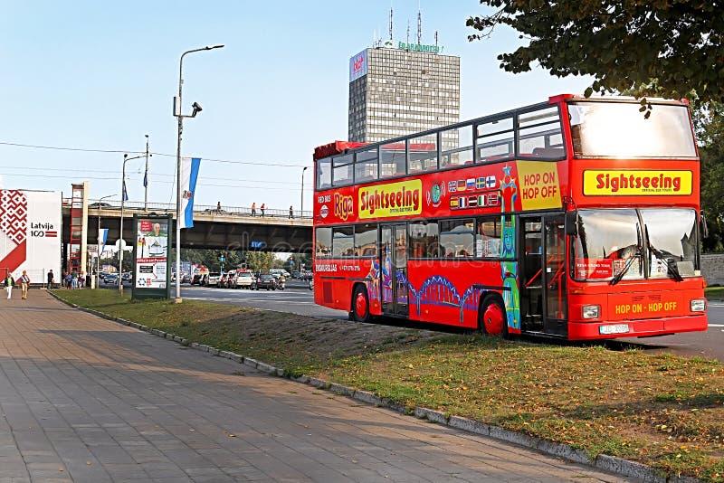 Τουριστικό κόκκινο διόροφο λεωφορείο λυκίσκος-λυκίσκος-από το τουριστηκό λεωφορείο επίσκεψης πόλεων στην οδό της πόλης της Ρήγας  στοκ φωτογραφίες