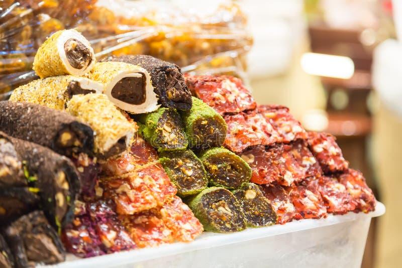 Τουρκικά γλυκά στην αιγυπτιακή bazaar αγορά στη Ιστανμπούλ, Τουρκία μαύρο στενό μαλακό επάνω λευκό μαξιλαριών μικροφώνων ακουστικ στοκ εικόνα