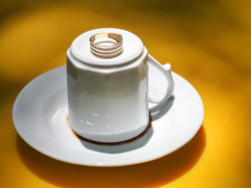 Τουρκικά κρεμαστό κόσμημα φλυτζανιών καφέ και γαμήλιο δαχτυλίδι σε το στοκ εικόνα