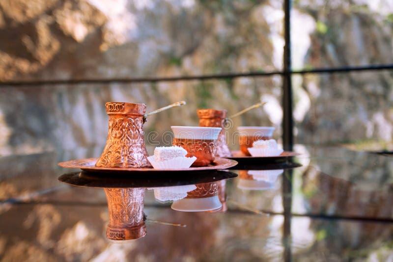 Τουρκικός καφές δύο στο χαλκό cezve με το κομμάτι του lokum στον πίνακα γυαλιού στοκ φωτογραφίες