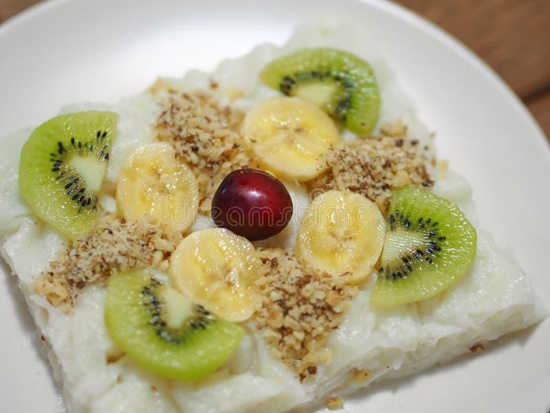 Τουρκικός-συγκεκριμένος αυξήθηκε γλυκό πουτίγκας gullac και ακτινίδιων και ξύλων καρυδιάς μπανανών μόρια στοκ εικόνα