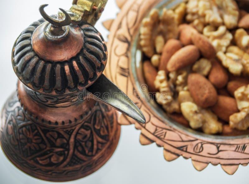 Τουρκικός χαλκός cookware χειροποίητος από τους Τούρκους και το πιάτο καραμελών με τα αμύγδαλα και τα ξύλα καρυδιάς στοκ φωτογραφία με δικαίωμα ελεύθερης χρήσης