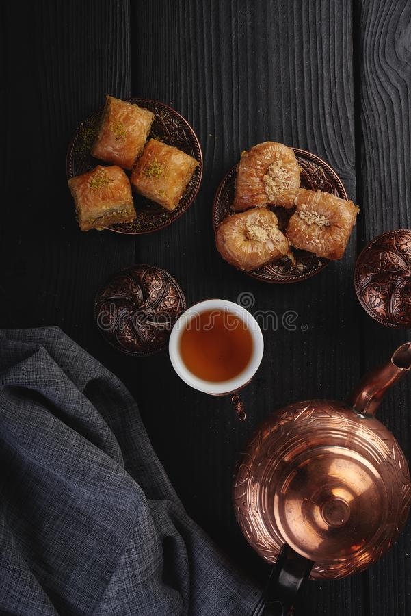 Τουρκικό παραδοσιακό επιδόρπιο Baklava με το τσάι στο σκοτεινό υπόβαθρο Φρέσκο και υγιές επιδόρπιο στοκ εικόνες