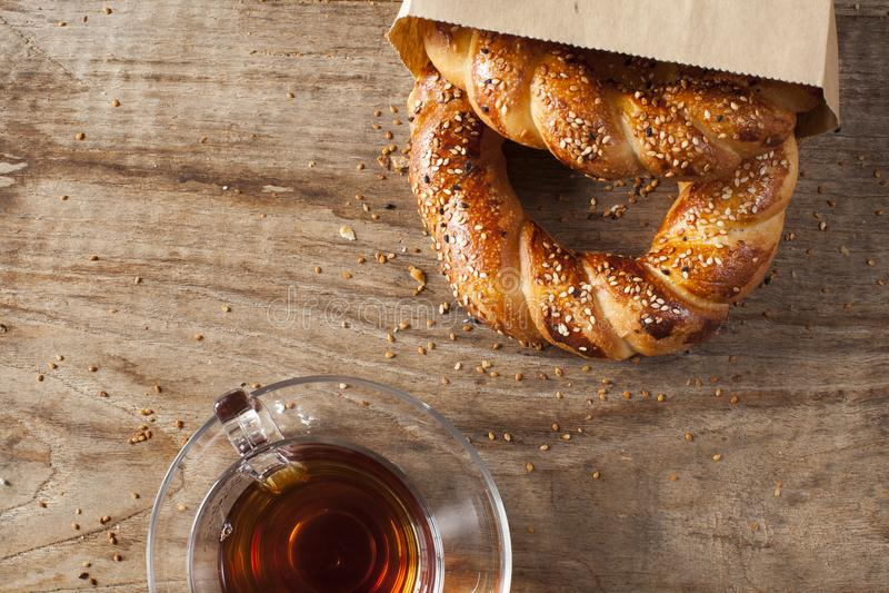 Τουρκικό bagel Simit στην τσάντα εγγράφου με τα παραδοσιακά γυαλιά τσαγιού στον ξύλινο πίνακα στοκ εικόνα με δικαίωμα ελεύθερης χρήσης