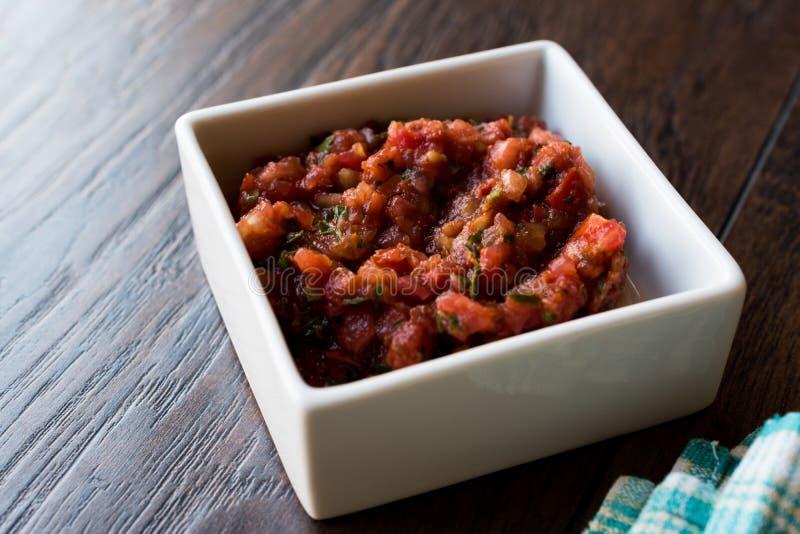 Τουρκικό Meze Acili Ezme ή acuka έκανε με τις φρέσκα ντομάτες και τα καρυκεύματα στο τετραγωνικό κεραμικό κύπελλο στοκ εικόνες