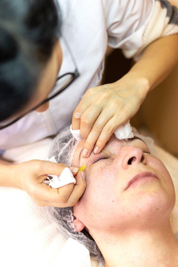 Του προσώπου επεξεργασία στο κέντρο SPA Νέα γυναίκα που έχει μια του προσώπου καλλυντική επεξεργασία στοκ εικόνα