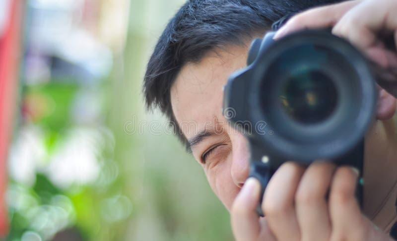 Του προσώπου κινηματογράφηση σε πρώτο πλάνο του αρσενικού φωτογράφου που παίρνει τις φωτογραφίες στοκ φωτογραφία