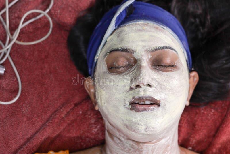 Του προσώπου μάσκα πακέτων που εφαρμόζεται στο πρόσωπο μιας κυρίας με τη ζώνη τρίχας με τις προσοχές ιδιαίτερες στοκ εικόνα με δικαίωμα ελεύθερης χρήσης