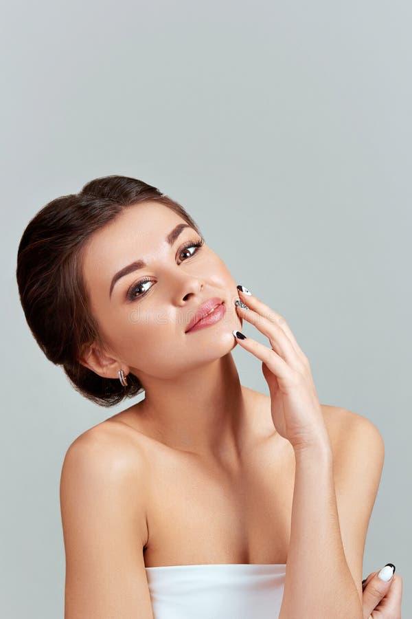 Του προσώπου προσοχή Θηλυκό που εφαρμόζει την κρέμα και το χαμόγελο Πρόσωπο ομορφιάς Πορτρέτο της νέας γυναίκας Κινηματογράφηση σ στοκ εικόνες