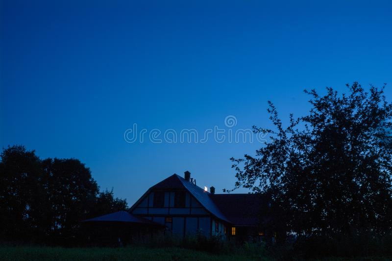 Του χωριού σπίτι με την καπνοδόχο και το ημισεληνοειδές φεγγάρι στοκ φωτογραφία με δικαίωμα ελεύθερης χρήσης