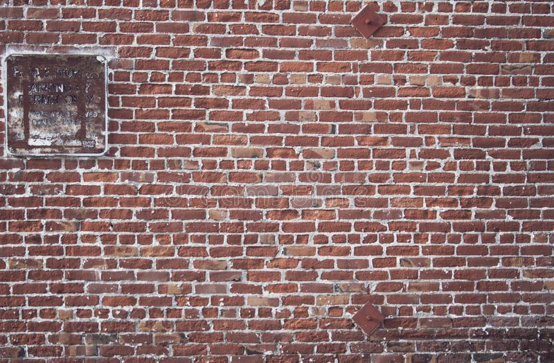 Τούβλινος τοίχος με το φορεμένο σημάδι χώρων στάθμευσης στοκ εικόνα με δικαίωμα ελεύθερης χρήσης