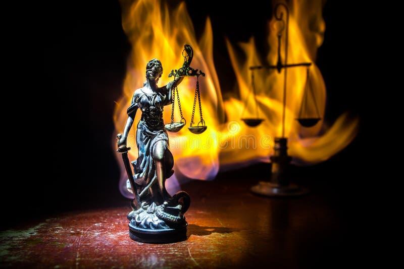 Το άγαλμα της δικαιοσύνης - γυναικείο δικαιοσύνη ή Iustitia/Justitia η ρωμαϊκή θεά της δικαιοσύνης σε ένα σκοτεινό υπόβαθρο πυρκα στοκ εικόνες