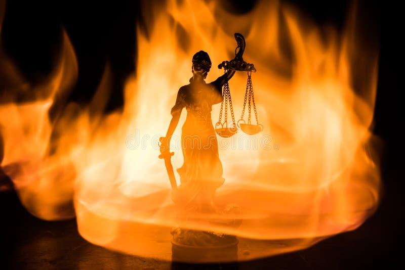 Το άγαλμα της δικαιοσύνης - γυναικείο δικαιοσύνη ή Iustitia/Justitia η ρωμαϊκή θεά της δικαιοσύνης σε ένα σκοτεινό υπόβαθρο πυρκα στοκ εικόνα