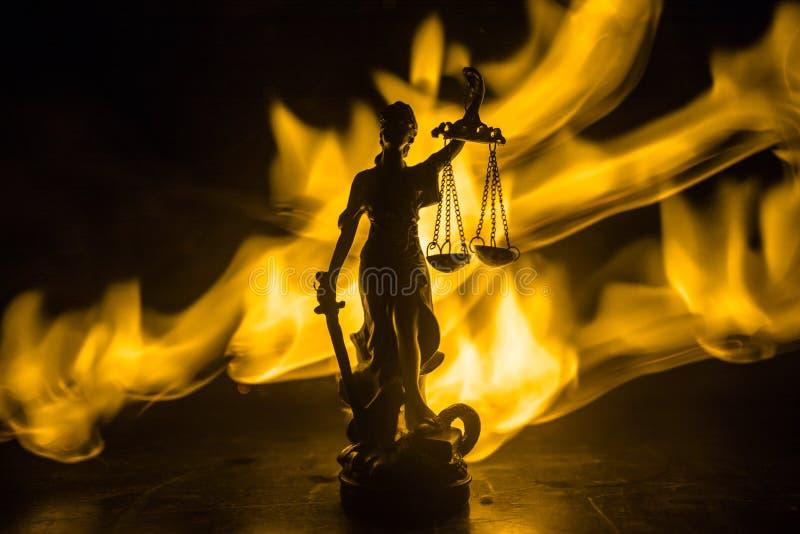 Το άγαλμα της δικαιοσύνης - γυναικείο δικαιοσύνη ή Iustitia/Justitia η ρωμαϊκή θεά της δικαιοσύνης σε ένα σκοτεινό υπόβαθρο πυρκα στοκ φωτογραφίες