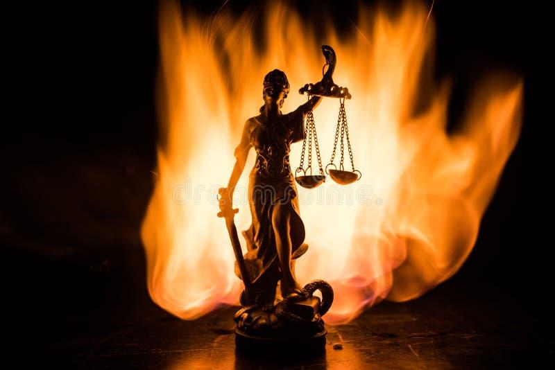 Το άγαλμα της δικαιοσύνης - γυναικείο δικαιοσύνη ή Iustitia/Justitia η ρωμαϊκή θεά της δικαιοσύνης σε ένα σκοτεινό υπόβαθρο πυρκα στοκ φωτογραφία με δικαίωμα ελεύθερης χρήσης