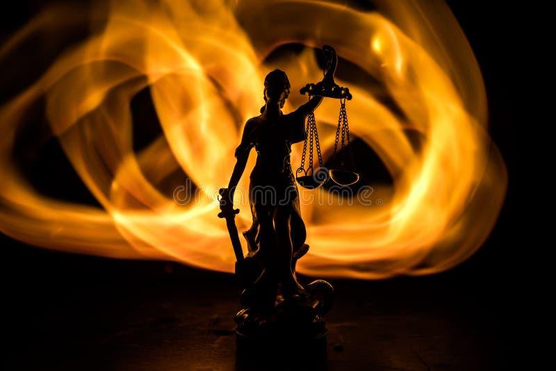 Το άγαλμα της δικαιοσύνης - γυναικείο δικαιοσύνη ή Iustitia/Justitia η ρωμαϊκή θεά της δικαιοσύνης σε ένα σκοτεινό υπόβαθρο πυρκα στοκ εικόνα με δικαίωμα ελεύθερης χρήσης