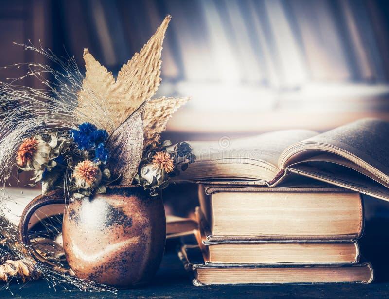 Το άνετο εγχώριο τοπίο με την ανθοδέσμη φθινοπώρου με τα φύλλα και την πτώση ανθίζει στο φλυτζάνι με το σωρό των βιβλίων στοκ εικόνες