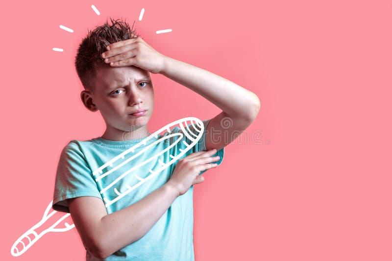 Το άρρωστο αγόρι στην ελαφριά μπλούζα μετρά τη θερμοκρασία ενός θερμομέτρου σε ένα χρωματισμένο υπόβαθρο στοκ εικόνα