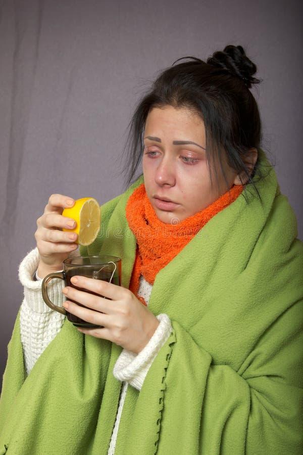 Το άρρωστο κορίτσι γρίπης πιέζει ένα λεμόνι στο τσάι σας στοκ φωτογραφία