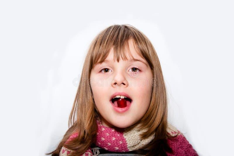 Το άρρωστο κορίτσι εφήβων με το μαντίλι παίρνει το κόκκινο χάπι στοκ εικόνες με δικαίωμα ελεύθερης χρήσης