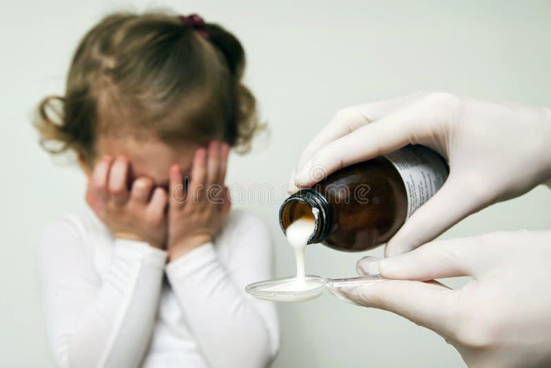 Το άρρωστο κοριτσάκι αναμένει το φάρμακό της που χύνει σε ένα κουτάλι στοκ εικόνες