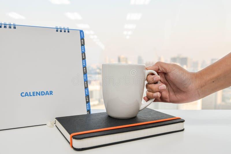 Το άσπρα ημερολόγιο και το χέρι κρατούν ένα φλιτζάνι του καφέ στοκ εικόνα