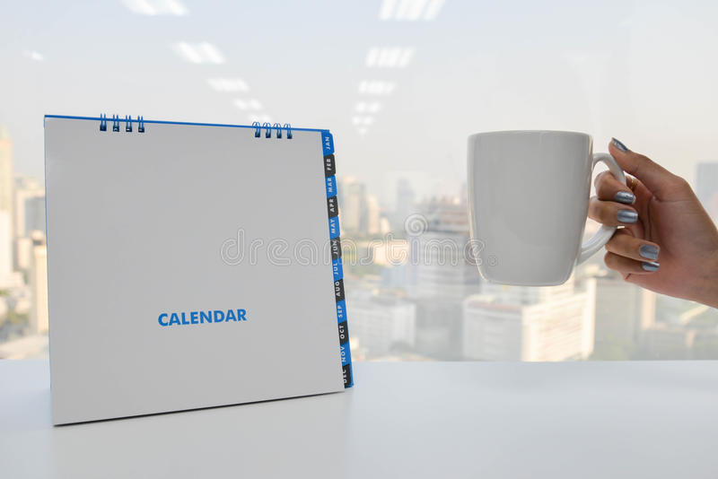 Το άσπρα ημερολόγιο και το χέρι κρατούν ένα φλιτζάνι του καφέ απεικόνιση αποθεμάτων