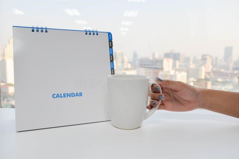 Το άσπρα ημερολόγιο και το χέρι κρατούν ένα φλιτζάνι του καφέ στοκ φωτογραφία