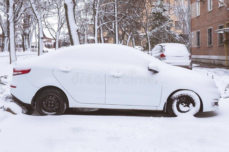 Το άσπρο αυτοκίνητο που καλύφθηκε με το χιόνι στάθμευσε κοντά στο σπίτι στοκ εικόνες με δικαίωμα ελεύθερης χρήσης