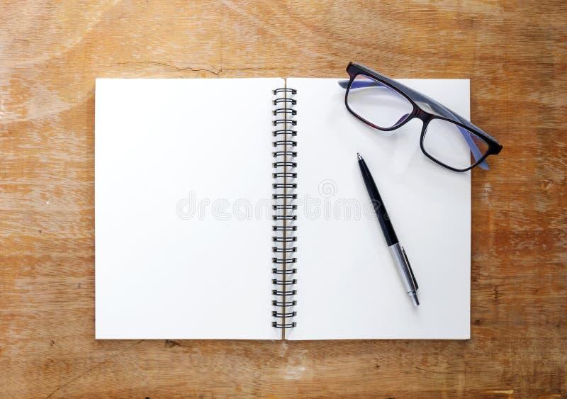 Το άσπρο βιβλίο τοποθετείται σε έναν ξύλινο πίνακα Υπάρχουν μάνδρες και glas στοκ φωτογραφία