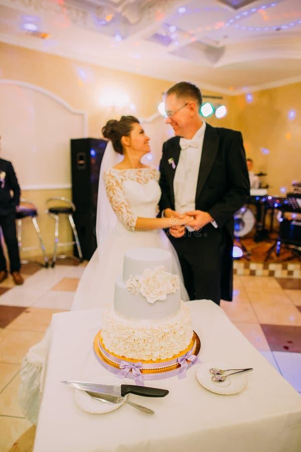Το άσπρο κέικ αμυγδαλωτού με τα λουλούδια στο υπόβαθρο των ευτυχών newlyweds στοκ εικόνες