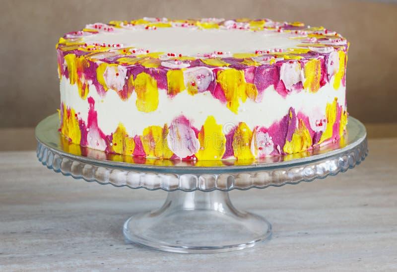 Το άσπρο κέικ γενεθλίων με ζωηρόχρωμο ψεκάζει πέρα από ένα ελαφρύ υπόβαθρο στοκ εικόνα