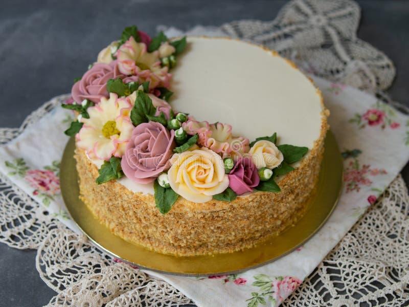 Το άσπρο κέικ μελιού κρέμας που διακοσμείται με το buttercream ανθίζει peonies, τριαντάφυλλα, χρυσάνθεμα, scabiosa στο γκρίζο υπό στοκ φωτογραφία με δικαίωμα ελεύθερης χρήσης