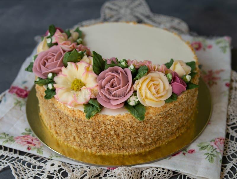 Το άσπρο κέικ μελιού κρέμας που διακοσμείται με το buttercream ανθίζει peonies, τριαντάφυλλα, χρυσάνθεμα, scabiosa στο γκρίζο υπό στοκ φωτογραφίες