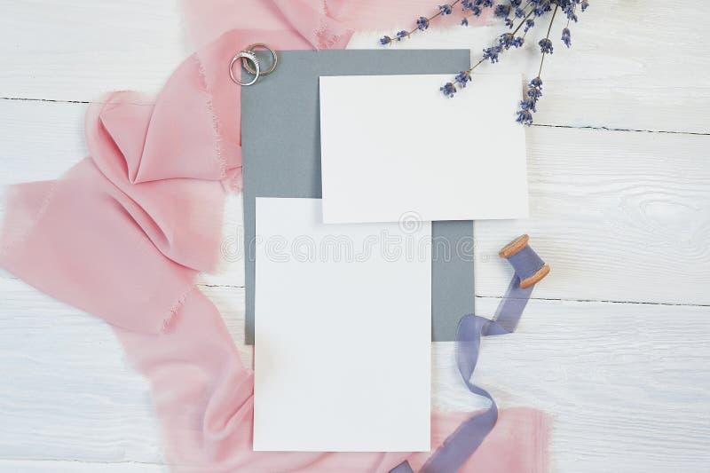 Το άσπρο κενό τόξο κορδελλών καρτών με δύο γαμήλια δαχτυλίδια σε ένα υπόβαθρο του ρόδινου και μπλε υφάσματος με lavender ανθίζει  στοκ εικόνα