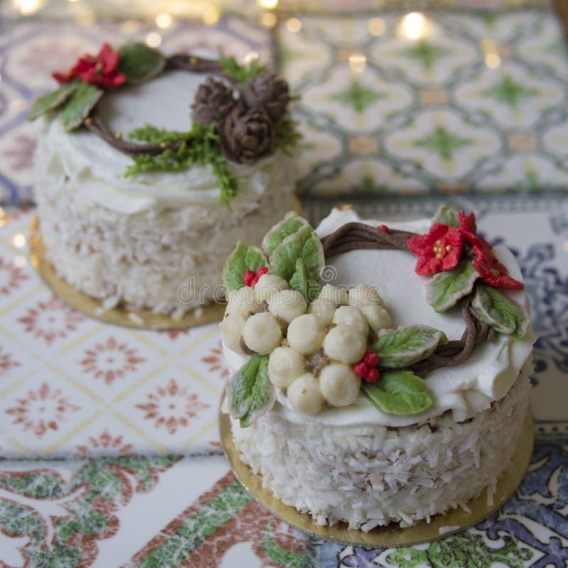 Το άσπρο νέο κέικ έτους ή Χριστουγέννων που διακοσμείται με το poinsettia κρέμας ανθίζει, κώνοι πεύκων, βαμβάκι και κομψοί κλαδίσ στοκ εικόνες