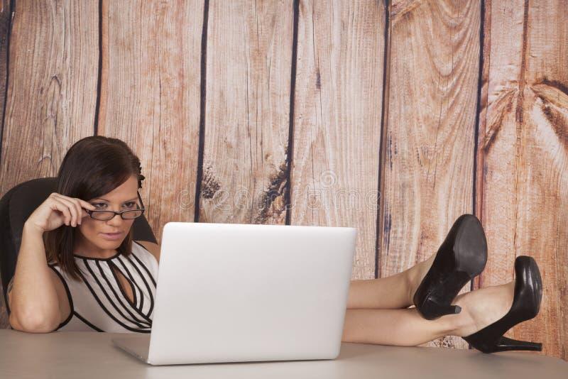 Το άσπρο ξύλο υπολογιστών φορεμάτων γυναικών κάθεται τα πόδια επάνω στοκ φωτογραφίες με δικαίωμα ελεύθερης χρήσης