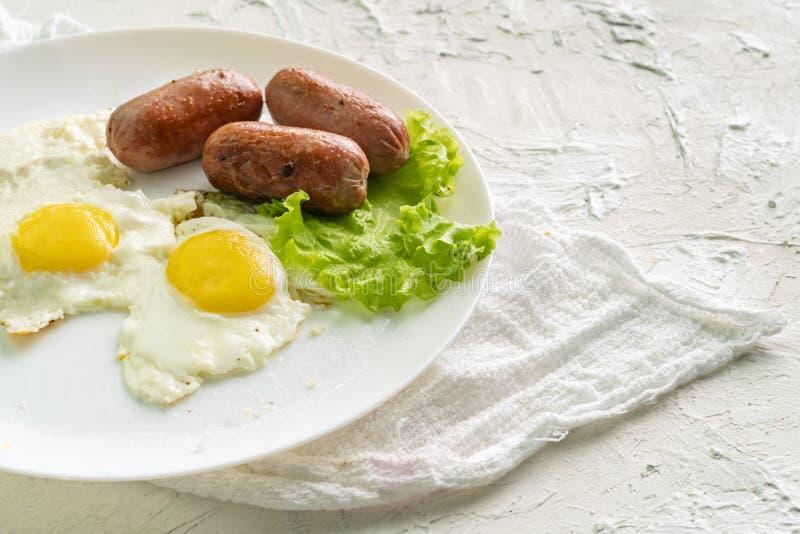 Το άσπρο πιάτο ή το πιάτο με το ελαφρύ πρόγευμα με τα λουκάνικα τηγάνισε τα αυγά και το μαρούλι, tablewares στοκ εικόνα