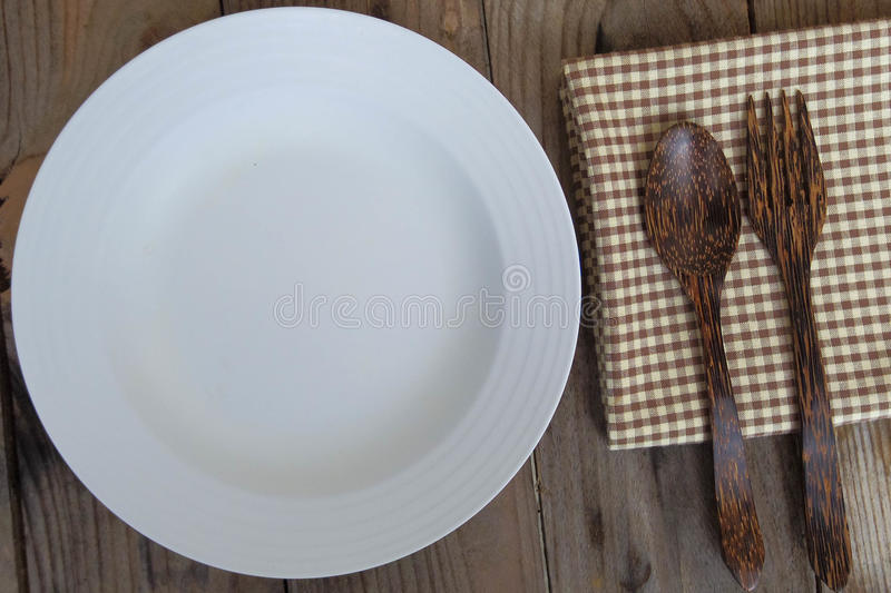 Το άσπρο πιάτο Empy με το δίκρανο βάζει στον ξύλινο πίνακα στοκ εικόνα με δικαίωμα ελεύθερης χρήσης