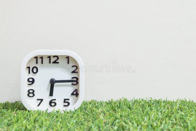 Το άσπρο ρολόι κινηματογραφήσεων σε πρώτο πλάνο για διακοσμεί παρουσιάζει ένα τέταρτο στις έξι ή 6:15 α Μ στο πράσινες τεχνητές π στοκ φωτογραφία