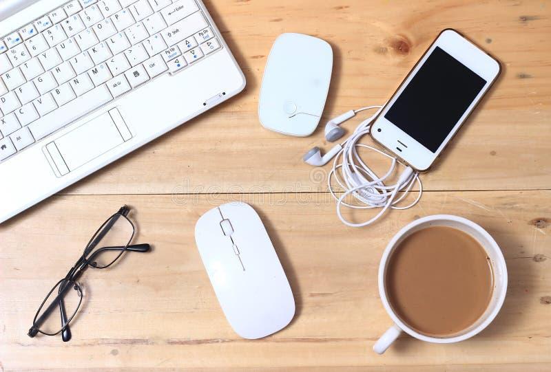 Το άσπρο σημειωματάριο, διαποδιαμορφωτής, ακουστικό, Smartphone, Eyeglass, καφές, ασύρματο ποντίκι στο ξύλινο γραφείο, βάζει οριζ στοκ φωτογραφία με δικαίωμα ελεύθερης χρήσης