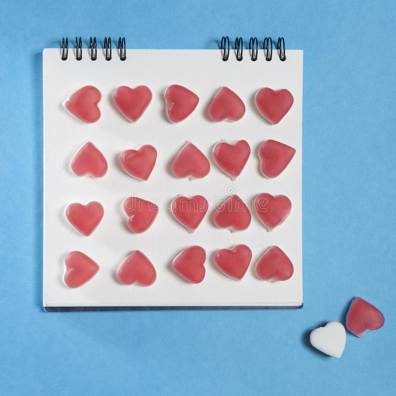 Το άσπρο σημειωματάριο στα ελατήρια με μια καρδιά marmelade σε ένα μπλε υπόβαθρο στοκ φωτογραφία με δικαίωμα ελεύθερης χρήσης
