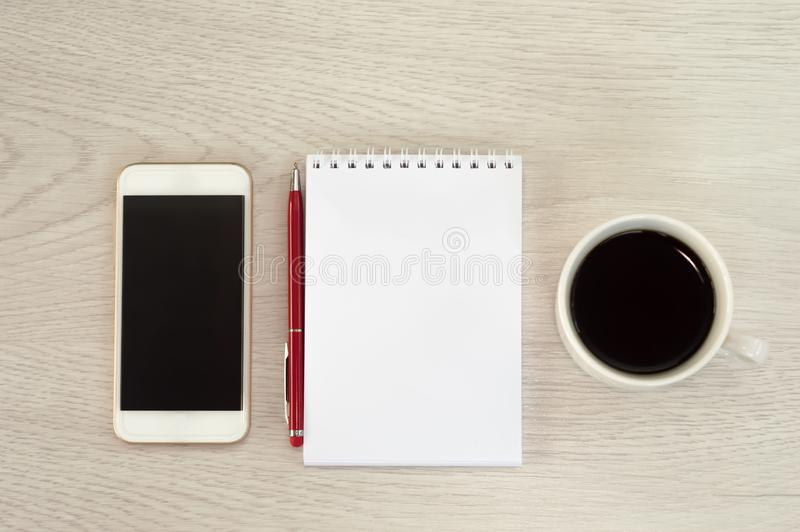 Το άσπρο τηλέφωνο με ένα φλιτζάνι του καφέ, το σημειωματάριο και η μάνδρα βρίσκονται σε έναν άσπρο ξύλινο πίνακα στοκ φωτογραφίες