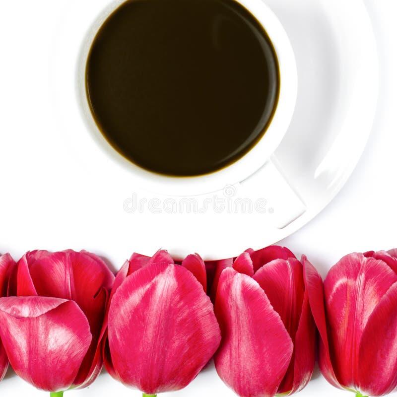 Το άσπρο φλυτζάνι καφέ στέκεται σε ένα άσπρο πιάτο με το άσπρο υπόβαθρο κοντά στις πολύχρωμες τουλίπες στοκ φωτογραφία με δικαίωμα ελεύθερης χρήσης