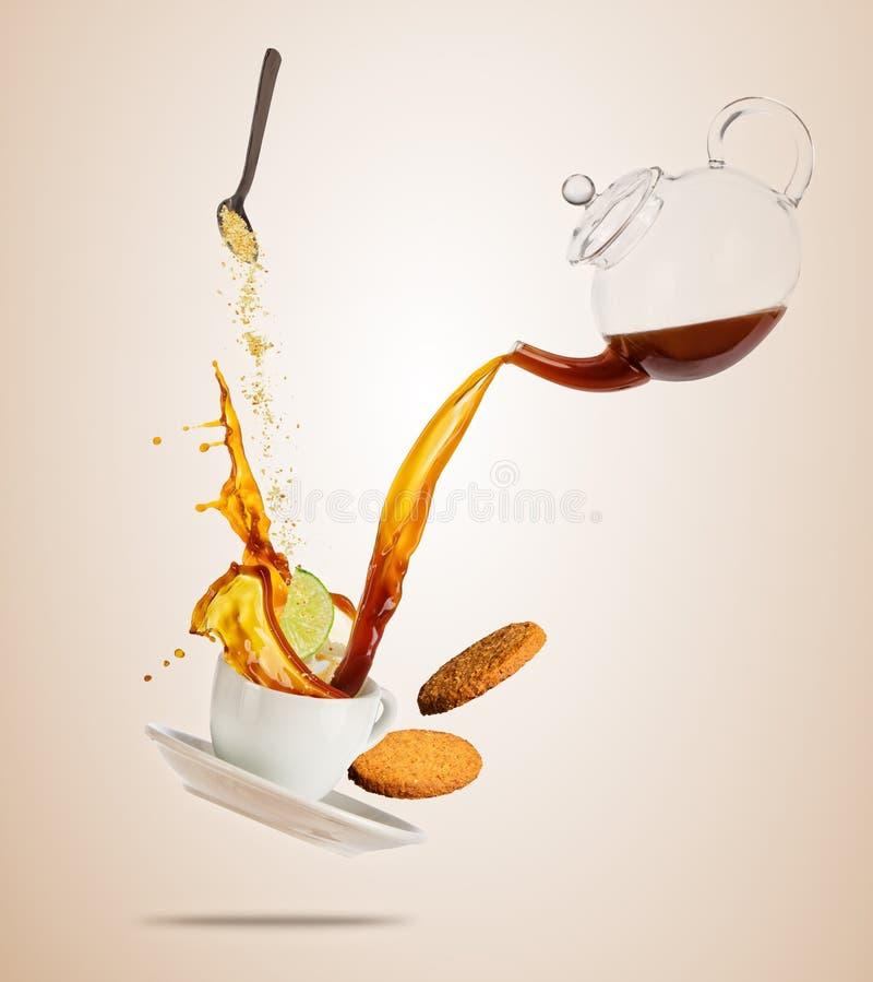 Το άσπρο φλυτζάνι Porcelaine με το ράντισμα του υγρού καφέ ή τσαγιού χώρισε στο καφετί υπόβαθρο στοκ εικόνες με δικαίωμα ελεύθερης χρήσης