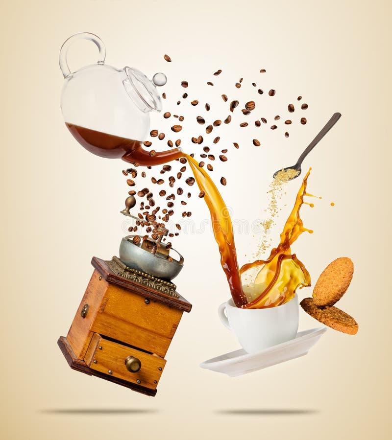 Το άσπρο φλυτζάνι Porcelaine με το ράντισμα του υγρού, του μύλου και των μπισκότων καφέ, χώρισε στο καφετί υπόβαθρο στοκ φωτογραφίες