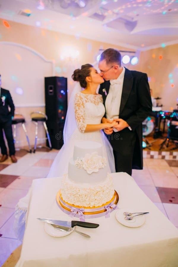 Το άσπρο floral γαμήλιο κέικ στο υπόβαθρο του φιλήματος το ζεύγος στοκ φωτογραφία με δικαίωμα ελεύθερης χρήσης
